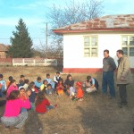 Steve Roy (standing right without a coat) with an interpreter teaches the school children. You can see Roxana sitting in the back row on the right with the children. John Lambert is in the front right corner of the picture taking a picture of the children.